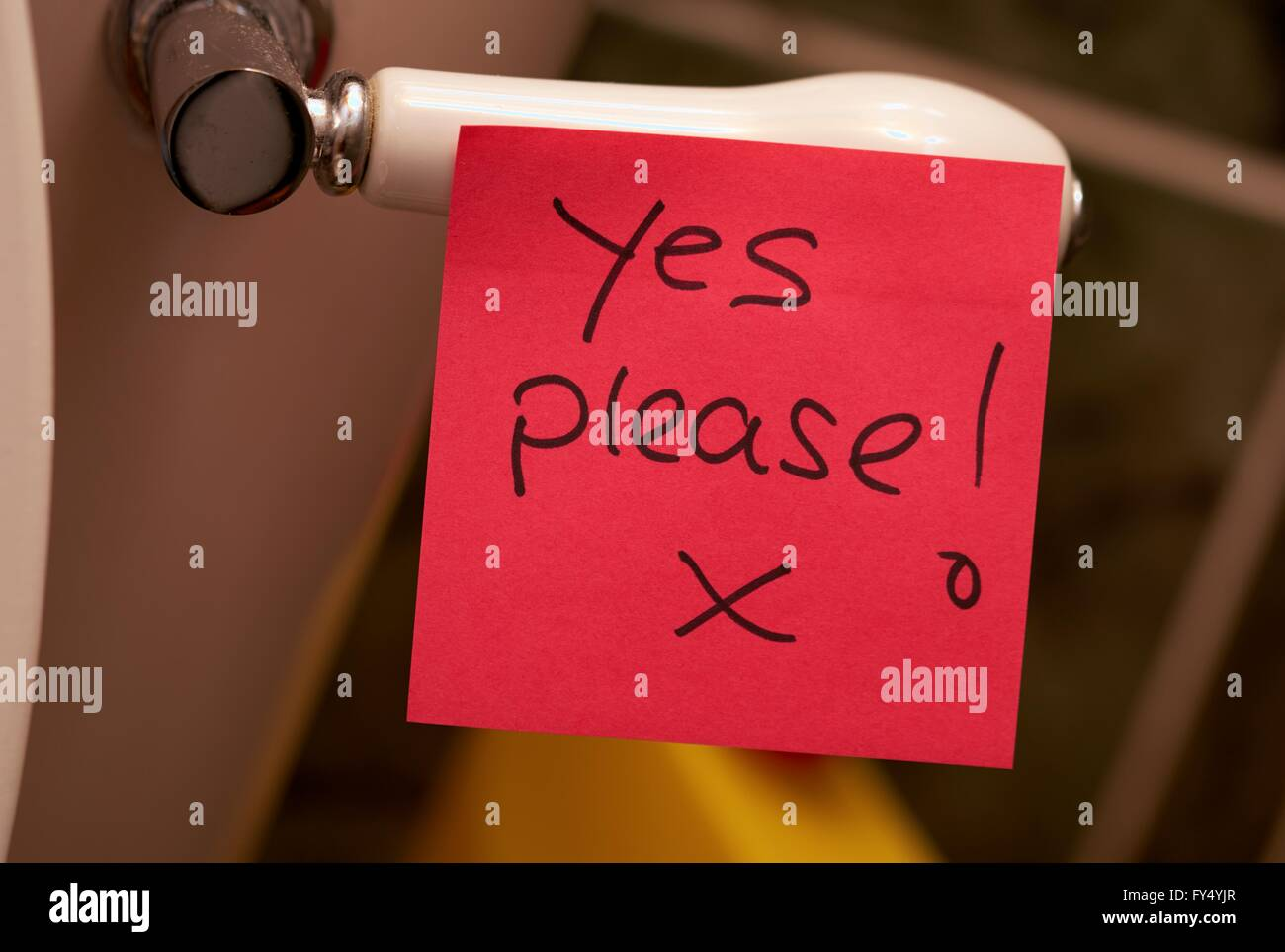 A post it note on a toilet handle with a hand written message yes please - Stock Image