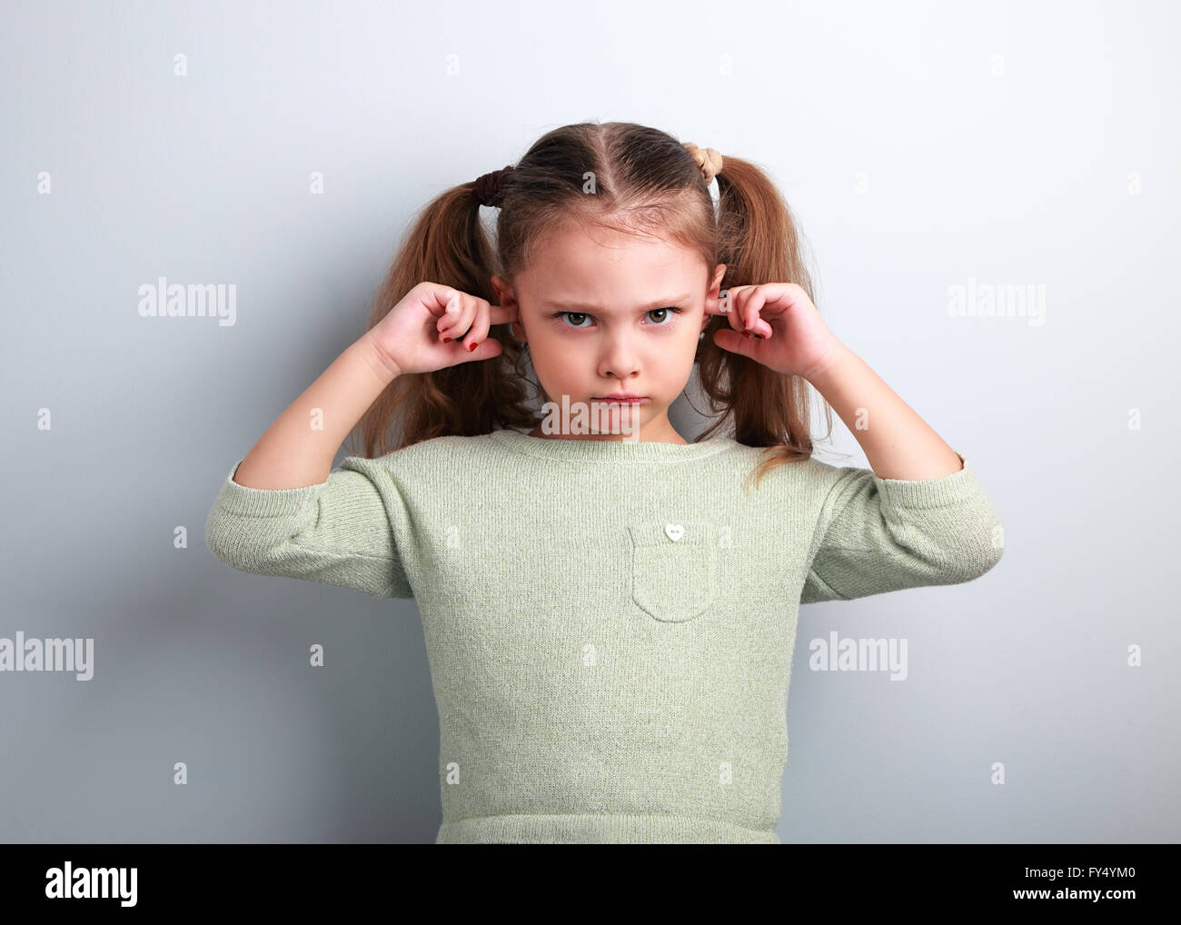 Angry unhappy kid girl covered ears the fingers and gesturing that not want to listen on blue background with empty - Stock Image