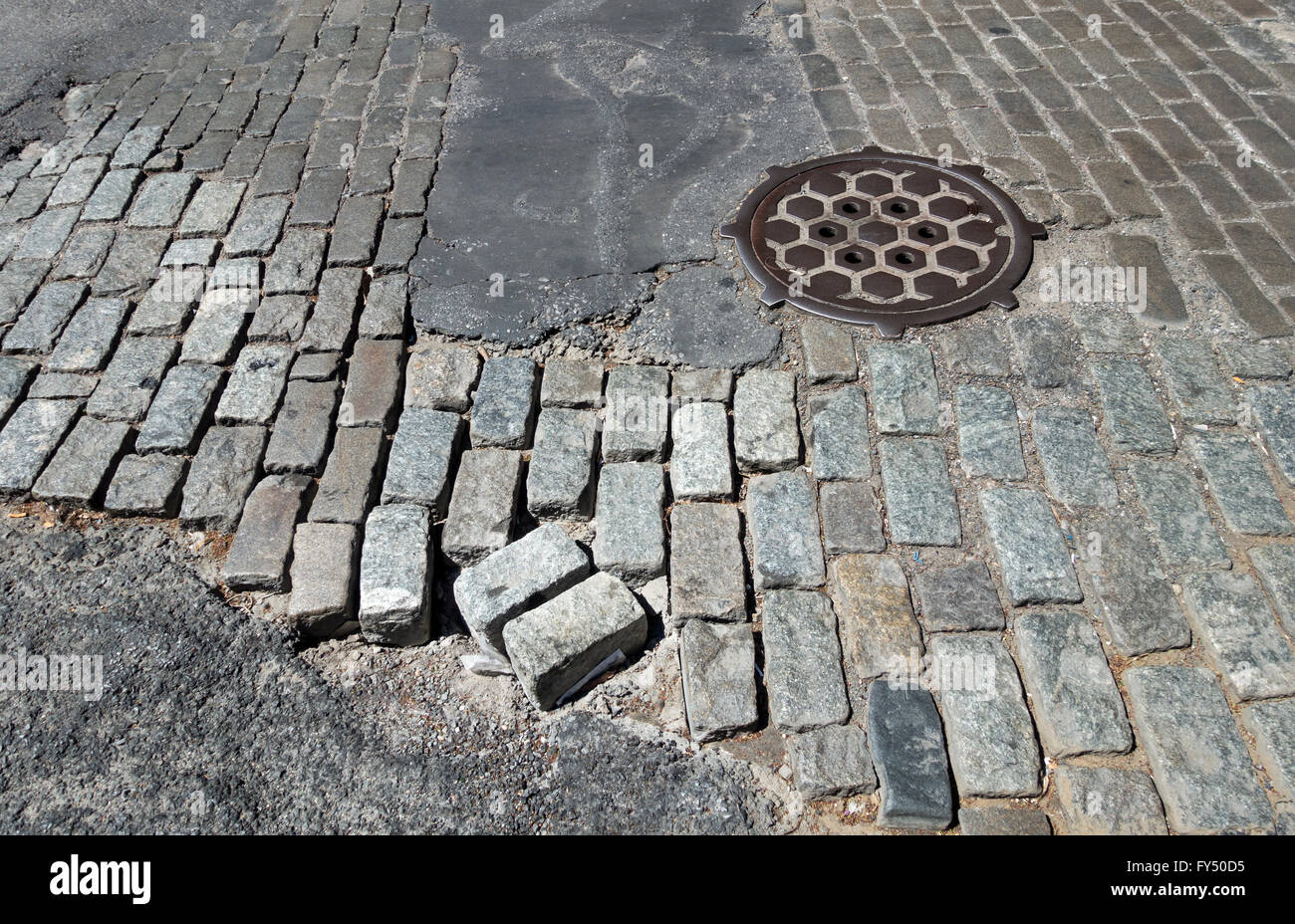 A mix of different types of cobblestones in disrepair on a street in Soho in Lower Manhattan in New York City - Stock Image