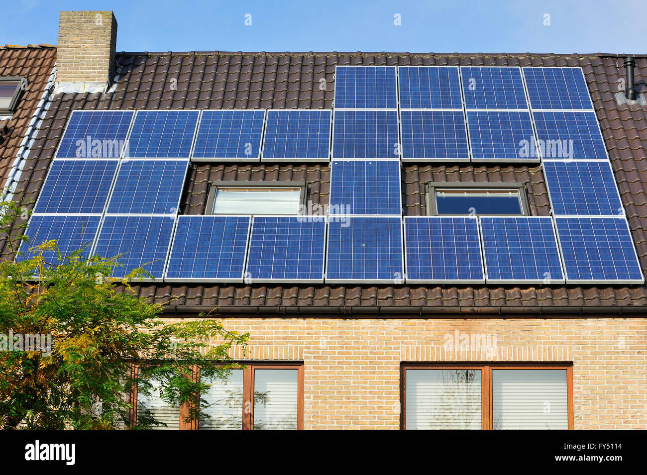 Photovoltaic solar panels / photovoltaic modules on roof of house - Stock Image
