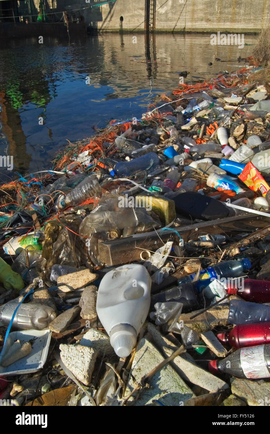 Plastic rubbish and other non-degradable waste in water of canal Stock Photo
