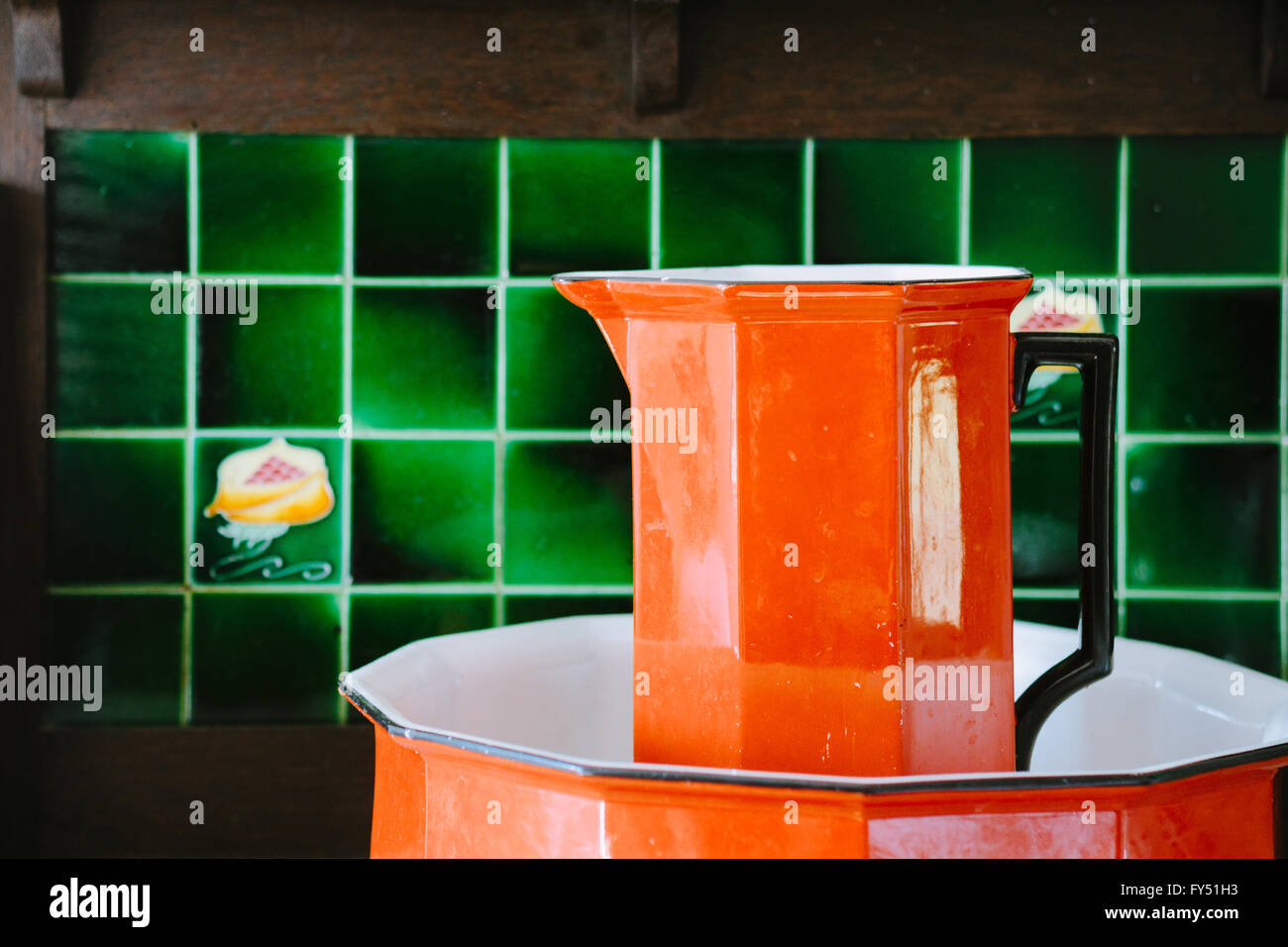 Vintage orange wash basin and sink with green tiles in the background. - Stock Image