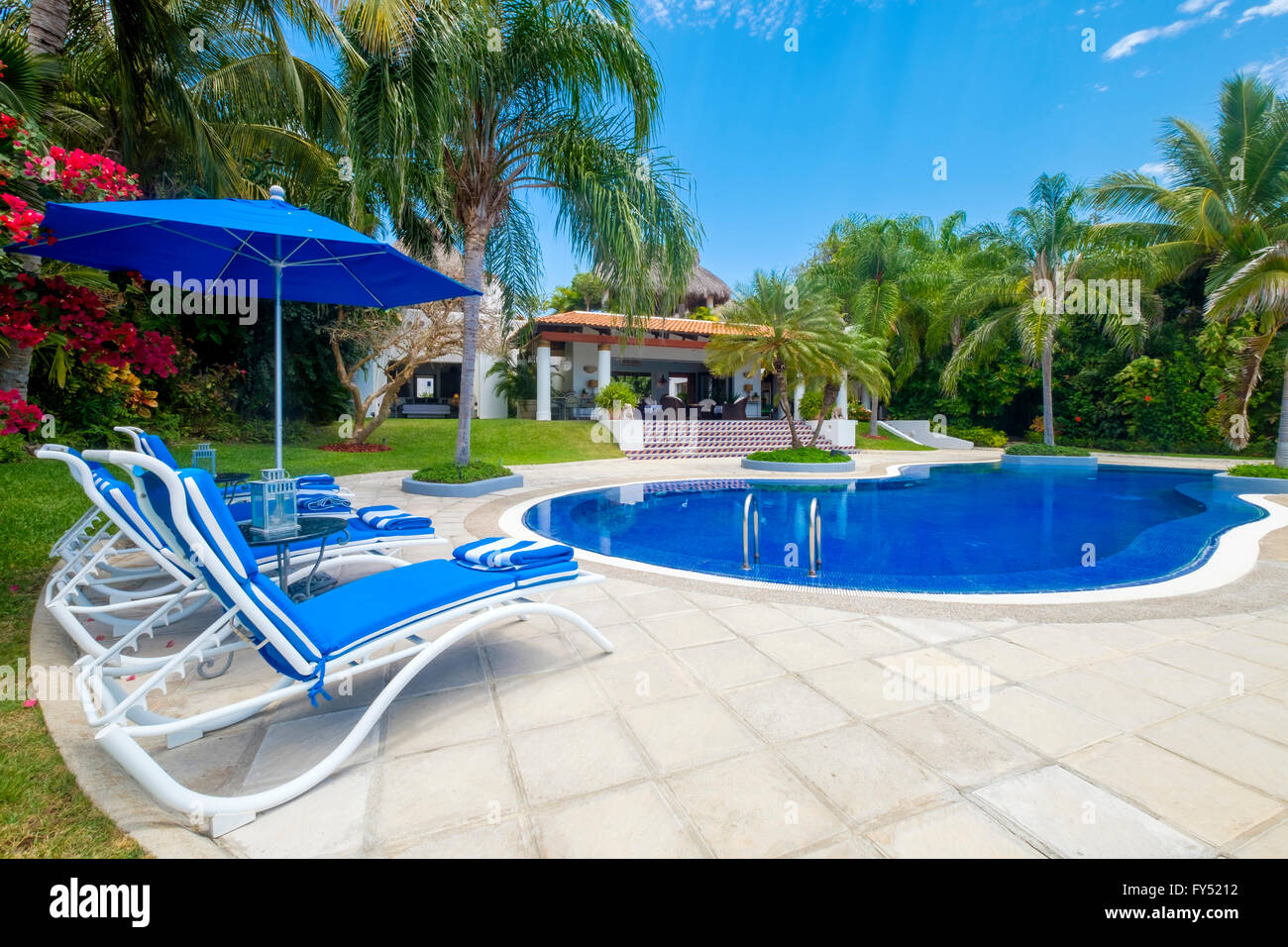 Swimming pool area with lounge chairs and umbrella - Upscale Mexican Residence, Punta de Mita, Riviera Nayarit, - Stock Image