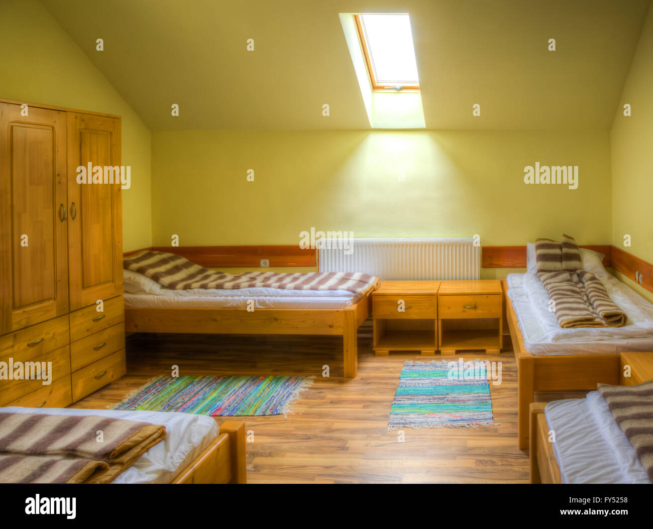 Clean hostel room with beds and wardrobe - Stock Image