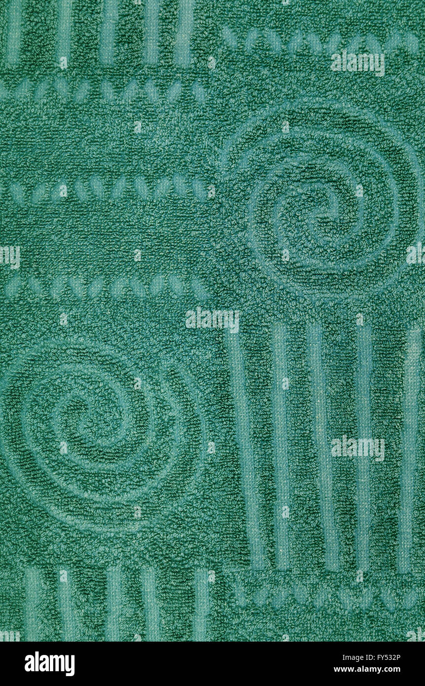 close up of a  green terry towel with geometrical and spiral pattern, vertical - Stock Image