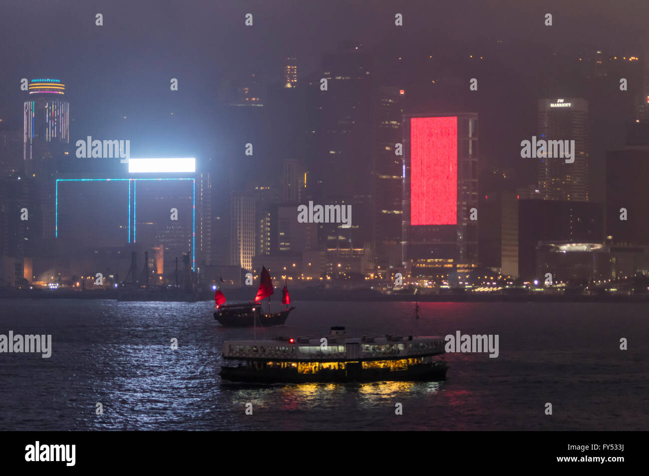 A Star Ferry and junk crossing Victoria Harbour between Hong Kong Island and Kowloon at night. - Stock Image