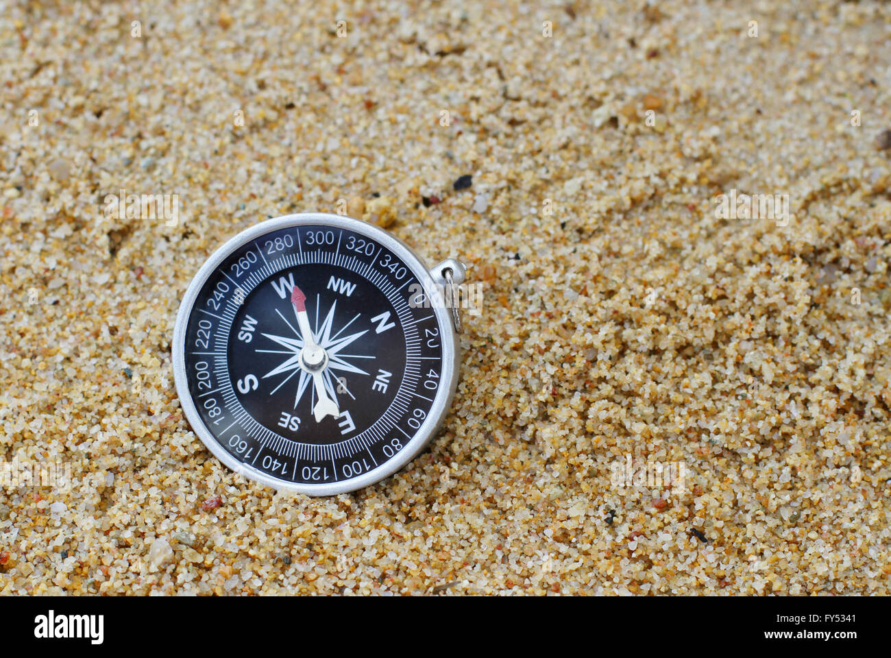 An old style compass pointing west resting on a sandy beach. - Stock Image