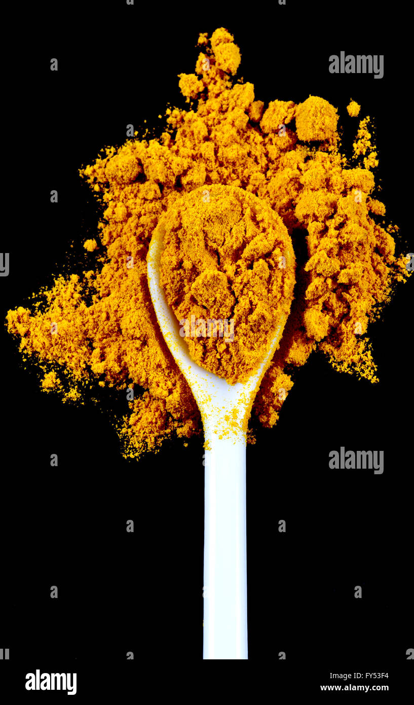 Ground turmeric spice in a white spoon isolated on a black background - Stock Image