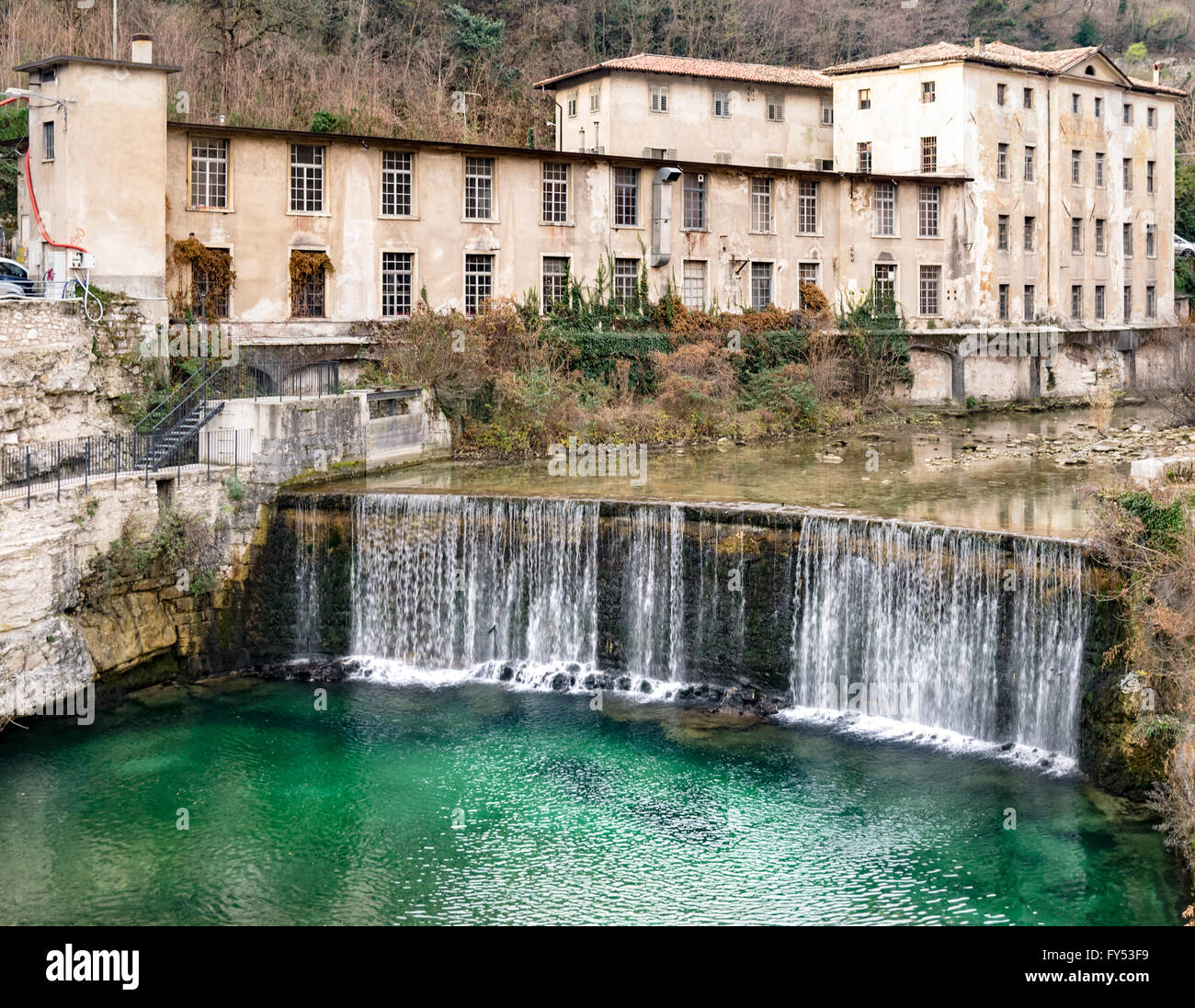 Old abandoned textile factory built on the river bank. - Stock Image