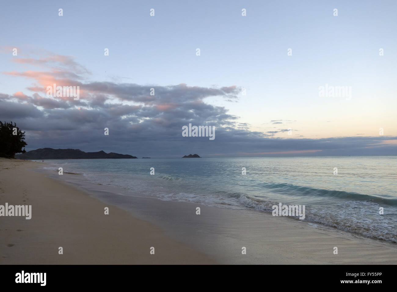 Gentle wave lap on Waimanalo Beach at dawn looking towards Mokulua islands on a nice day Oahu, Hawaii. - Stock Image