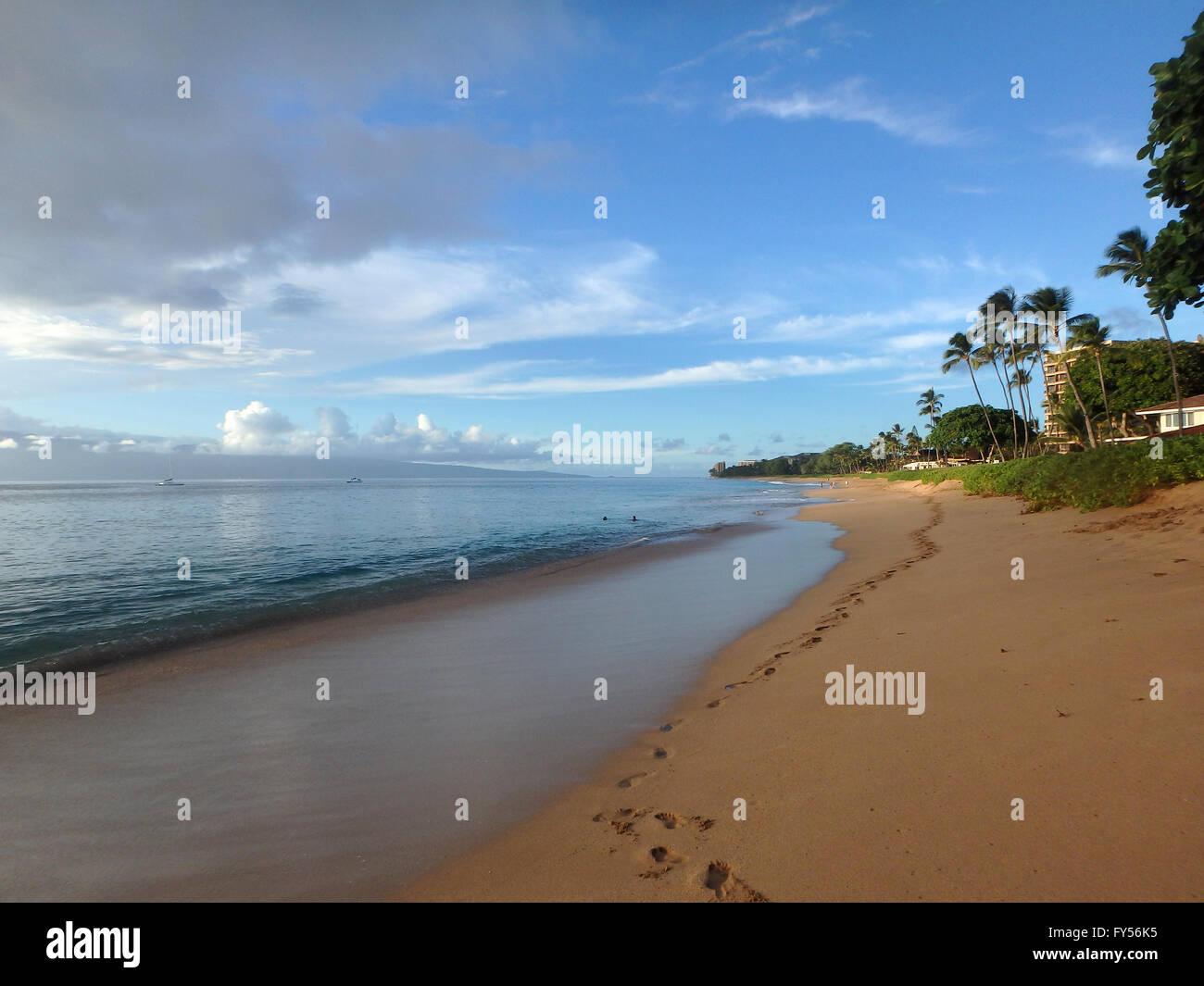 Kaanapali Beach at Dusk with gentle waves, boats in the water, foot prints and trees. Island of Lanai can be seen - Stock Image