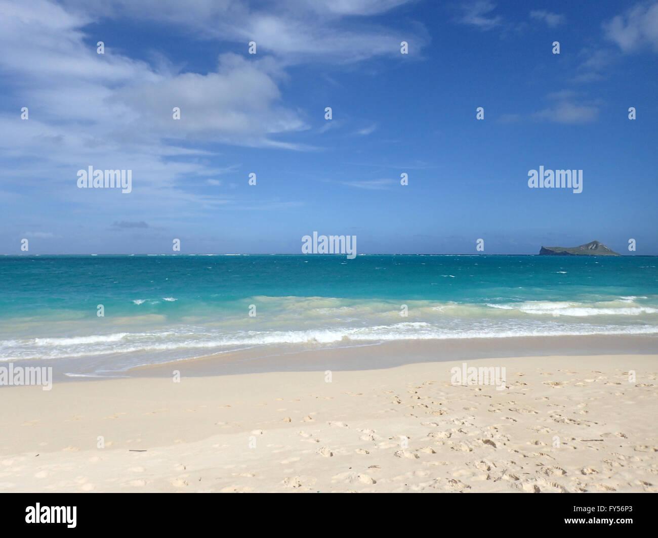 Gentle wave lap on white sand Waimanalo Beach looking towards Rabbit island on a nice day Oahu, Hawaii.  November - Stock Image