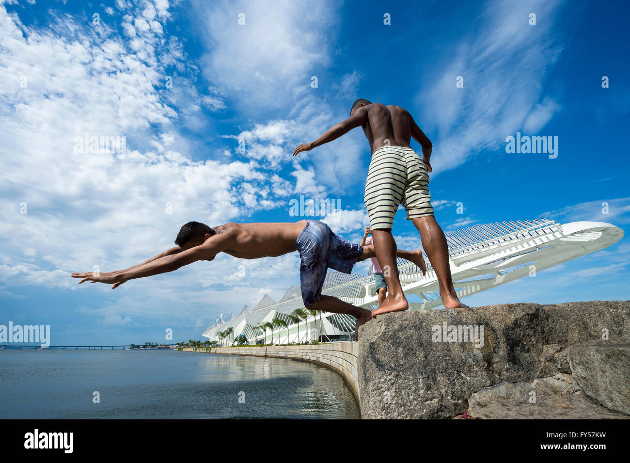 RIO DE JANEIRO - FEBRUARY 25, 2016: Young Brazilians jump into Guanabara Bay from the wall in front of the Museum - Stock Image
