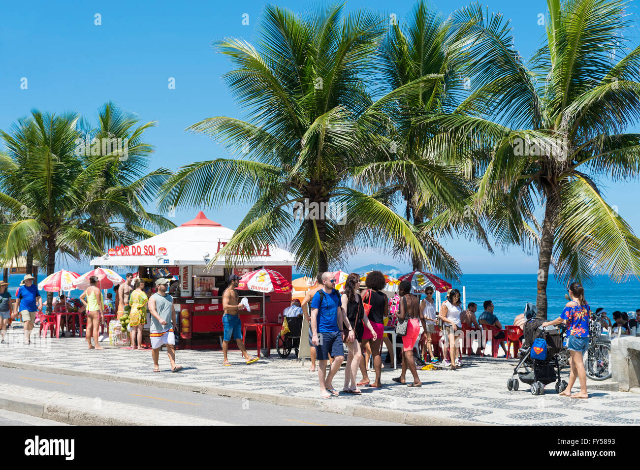 RIO DE JANEIRO, BRAZIL - MARCH 20, 2015: Brazilians relax at a kiosk selling coconuts overlooking Ipanema Beach. - Stock Image