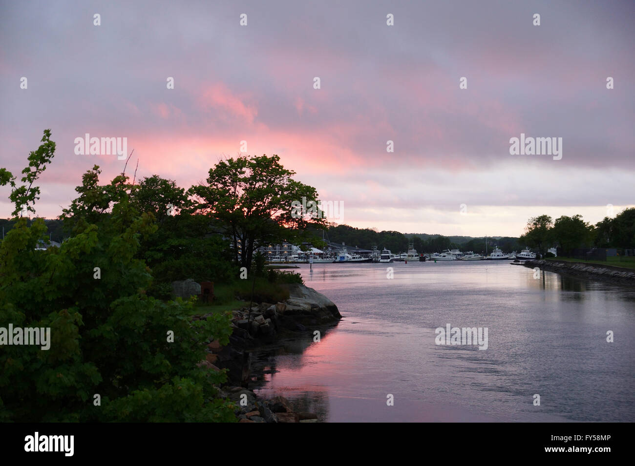 Sunset light shines over Blynman Canal reflects on the water with boats and buildings with trees behind them in - Stock Image