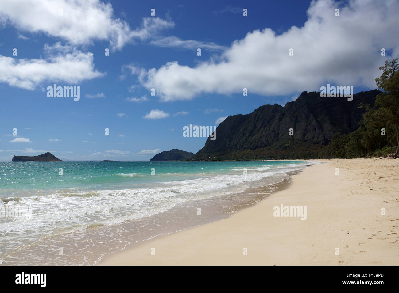 Gentle wave lap on Waimanalo Beach looking towards Rabbit island and Rock island on a nice day Oahu, Hawaii.  July - Stock Image