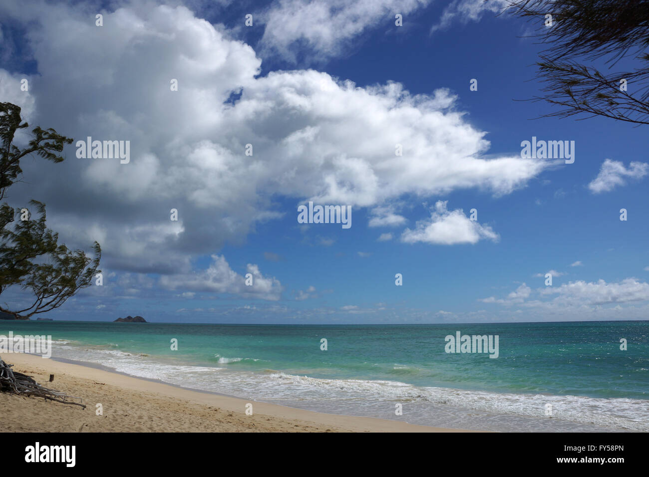 Gentle wave lap on Waimanalo Beach looking towards Mokulua islands on a nice day Oahu, Hawaii. July 2014. - Stock Image