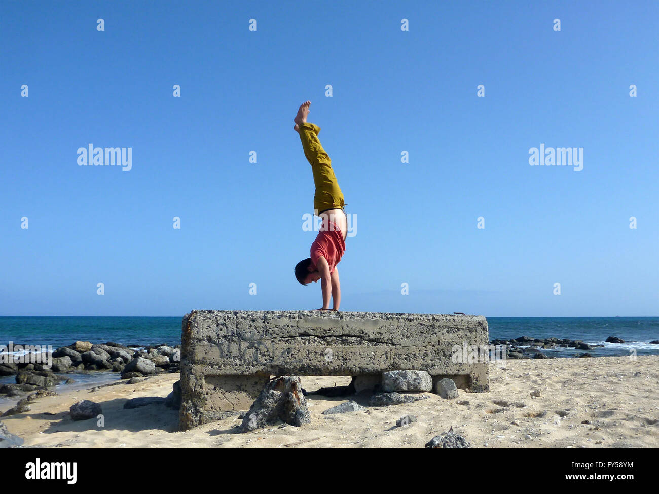Man wearing a red t-shirt, long olive pants, and bare feet Handstands on top a old historic pillbox on the beach - Stock Image
