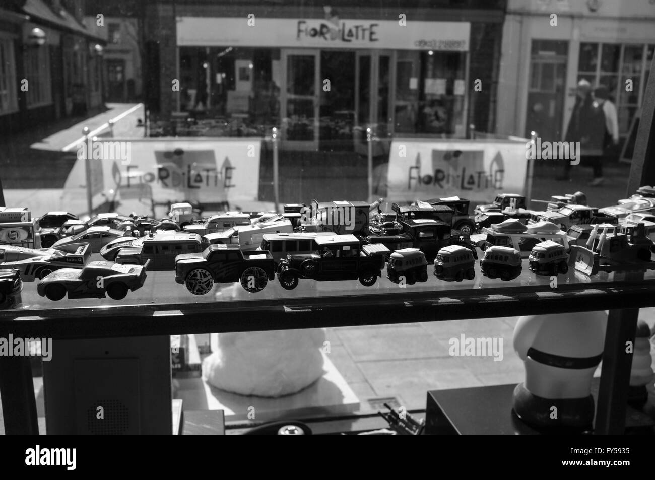A black and white image of old toy cars in the window of shop Stock Photo