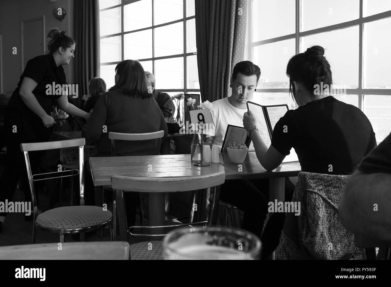 A black and white image of people studying menus - Stock Image