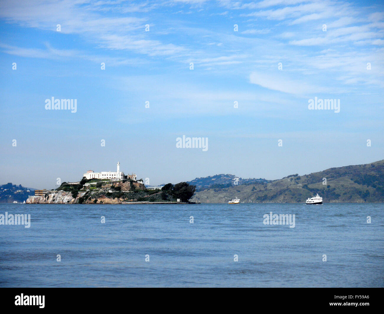 Infamous Alcatraz Island on a nice Day with a tour boat in front of it and Angel Island, Marin county in the distance - Stock Image