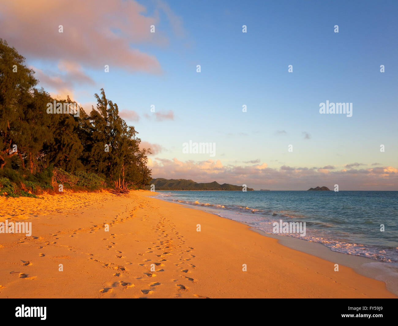 Gentle waves crash on Waimanalo Beach on Oahu, Hawaii at dawn with dramatic colors.  Looking north towards Lanikai - Stock Image