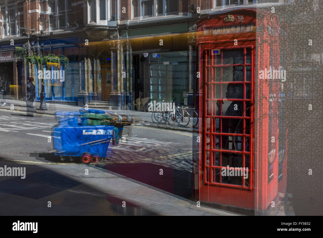 Seen through an office foyer window, including a receptionist appearing in red phone box kiosk. - Stock Image