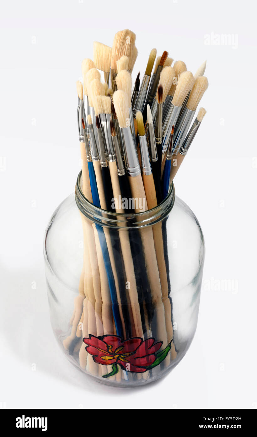 artists brushes in glass jar - Stock Image