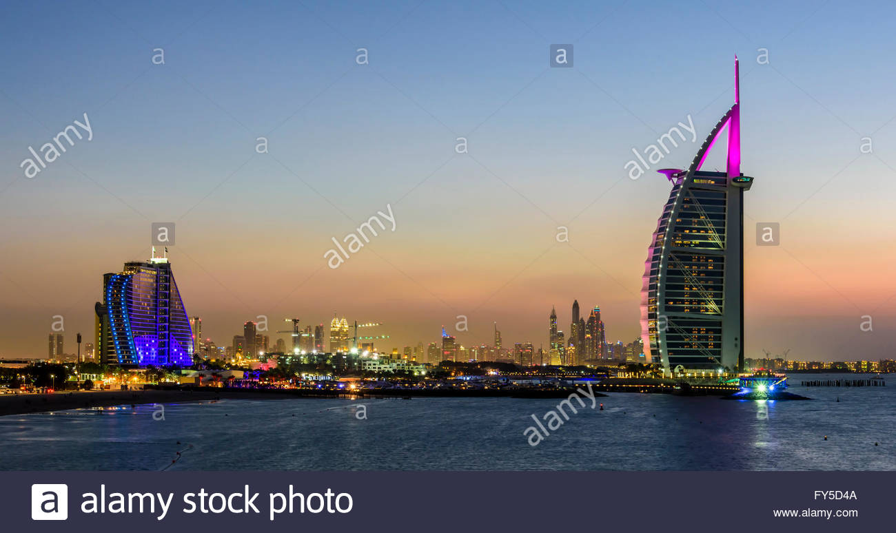 Sunset in Jumeirah, with on the left the Jumeirah Hotel, the Burj Al Arab and in the background the Marina of Dubai, - Stock Image