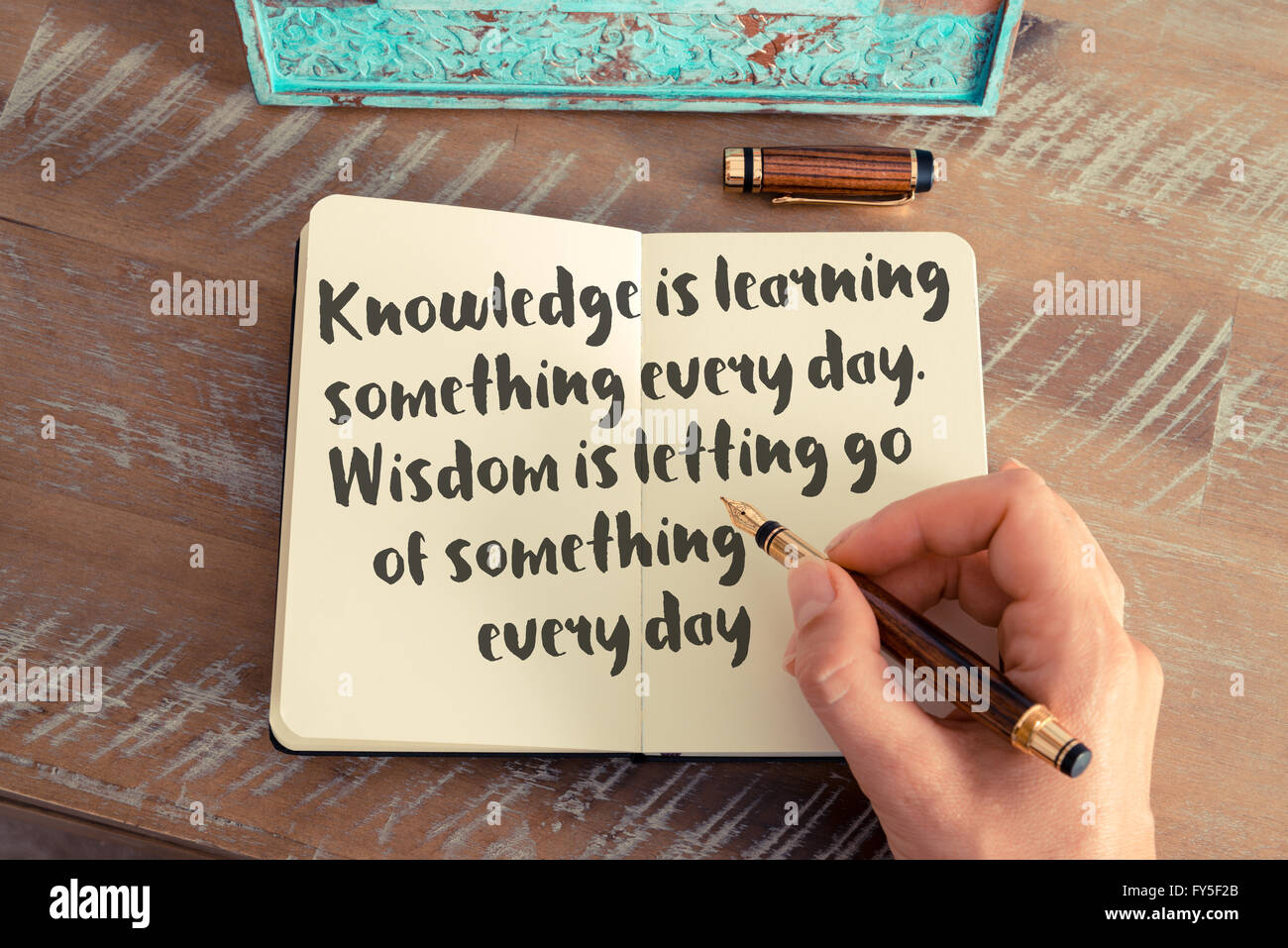 Handwritten quote Knowledge is learning something every day. Wisdom is letting go of something every day - Stock Image
