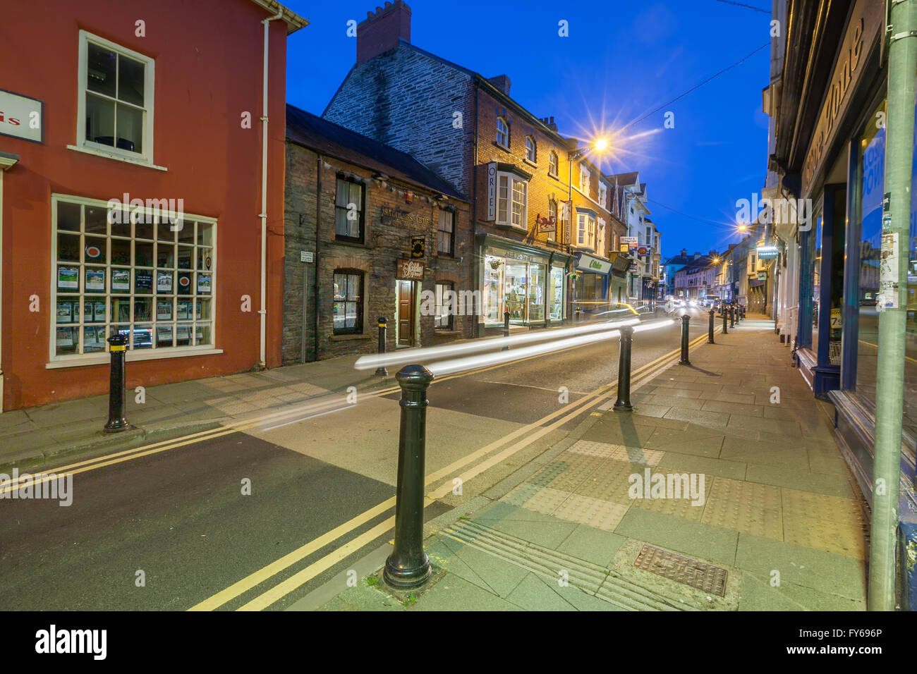 Cardigan High Street in Ceredigion, Wales.  Taken at twilight with traffic trails streaks of light. Stock Photo