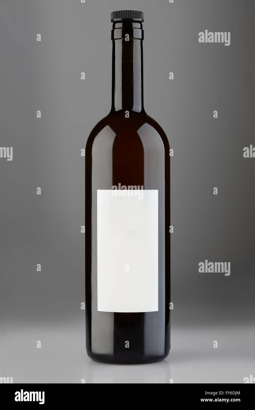 Red wine bottle with cap and blank label on gray background, clipping path - Stock Image
