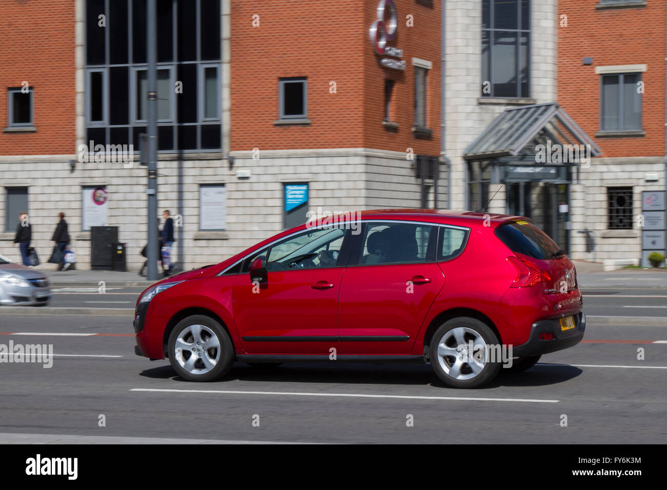 Red Peugeot 308 Traffic on 'The Strand' the main highway across the front of Liverpool City, adjacent to - Stock Image