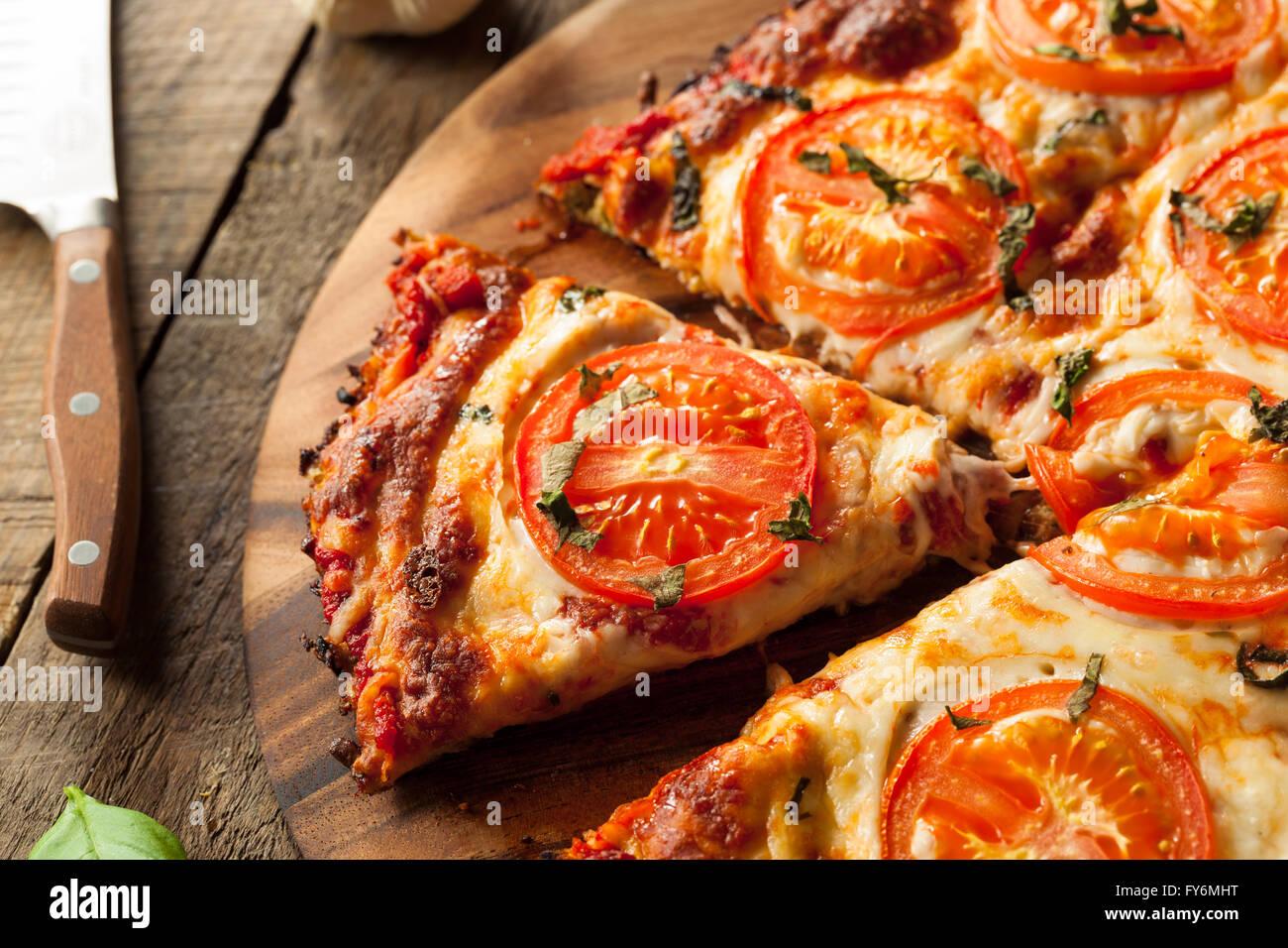 Homemade Vegan Cauliflower Crust Pizza with Tomato and Basil Stock Photo