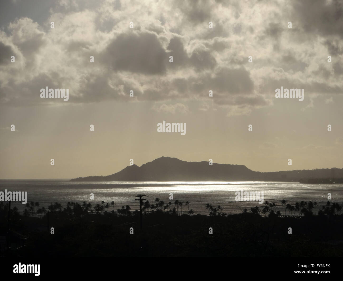 Light Shines through the clouds on Diamondhead at Dusk with Hawaii Kai in the foreground on Oahu, Hawaii. - Stock Image