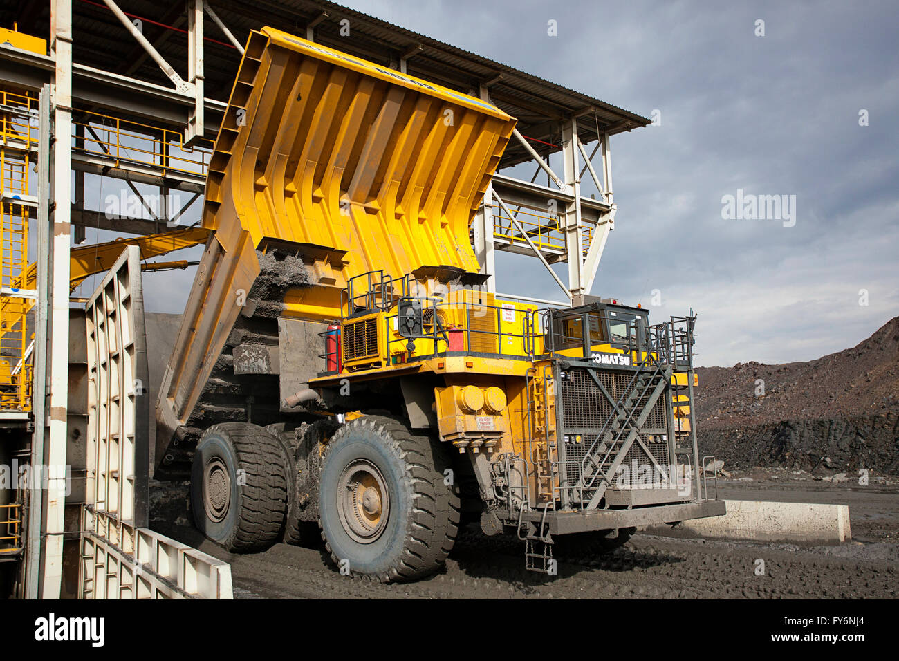 Large dump truck dumping copper ore into giant crusher - Stock Image