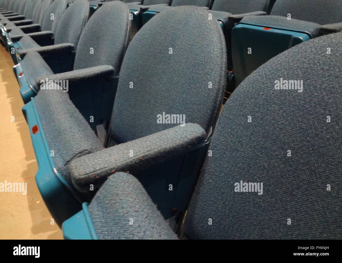 Curved Rows of Light Blue Cloth Seat with armrests in a theater. - Stock Image