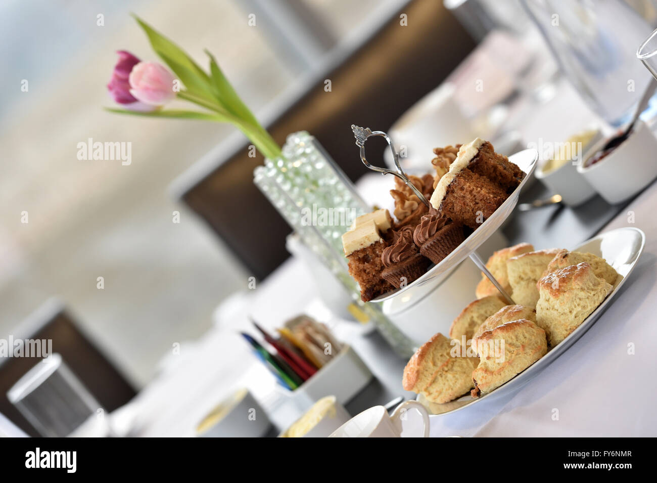 Afternoon tea in a business environment,tulips, scones and cakes - Stock Image