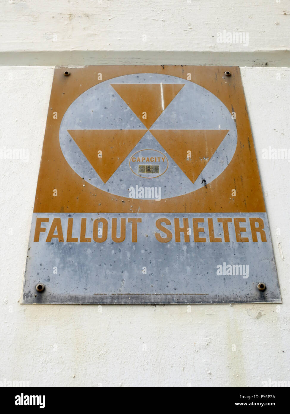 Old Fallout Shelter Sign from the cold war era slowly rusts as it hangs on wall. Stock Photo