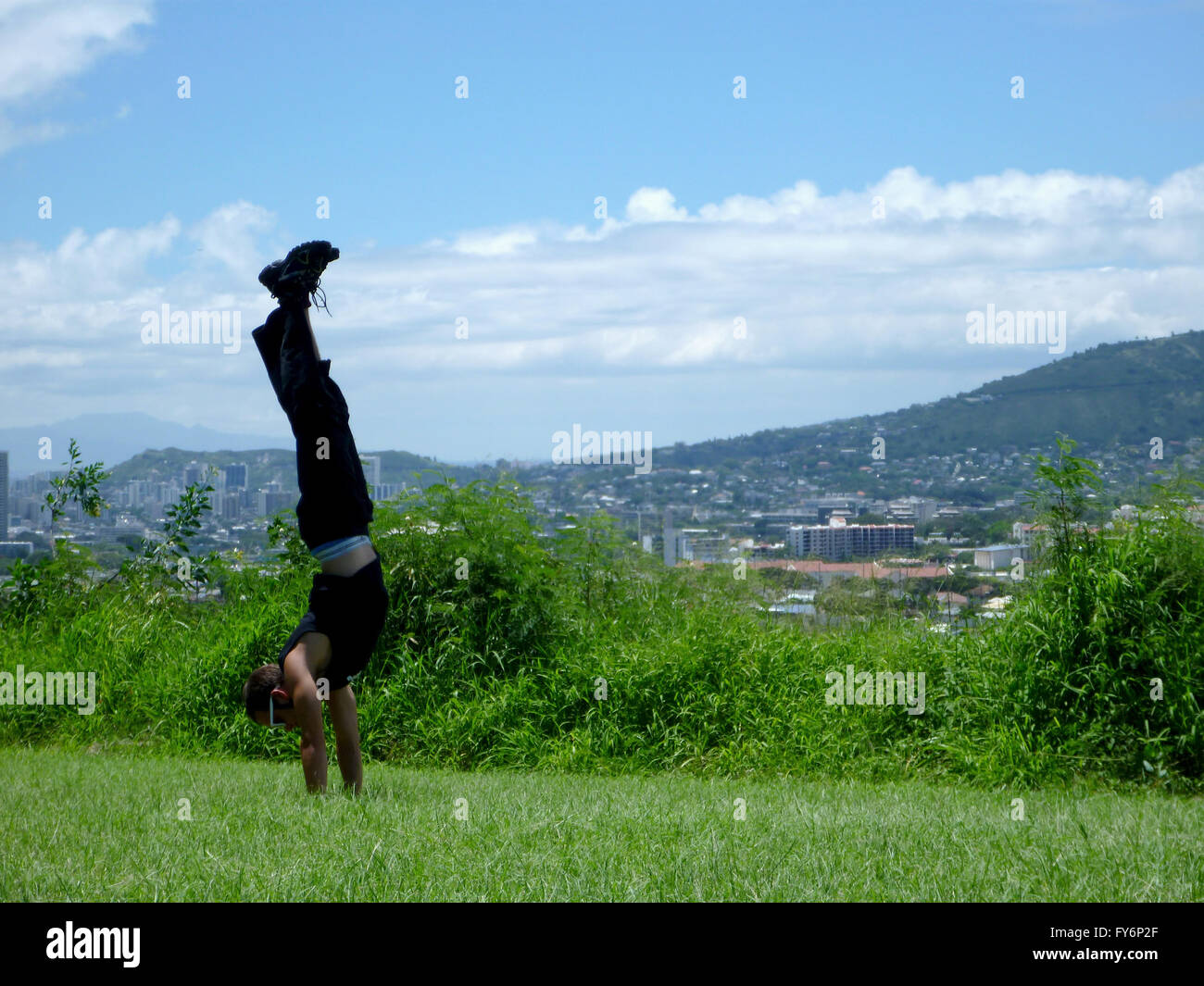 Man wearing sunglass, sleeveless shirt, long pants, and shoes does handstand in grass field with city of Honolulu - Stock Image