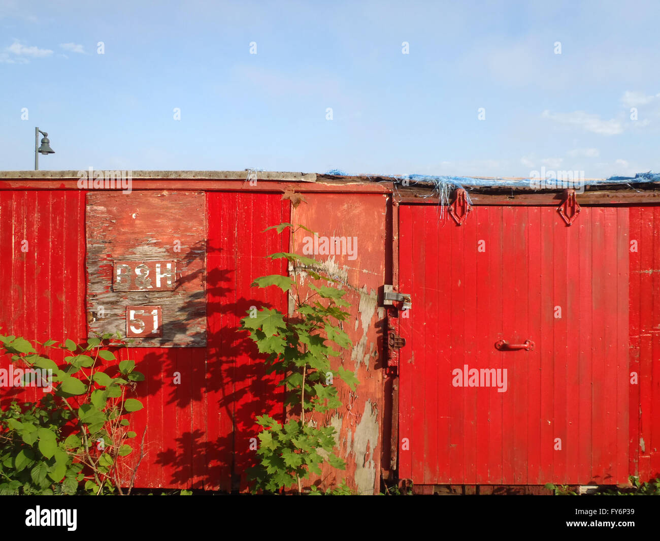 Old Red Rail cars with the word B & H 51 fade in the sun in Portland, Maine. - Stock Image