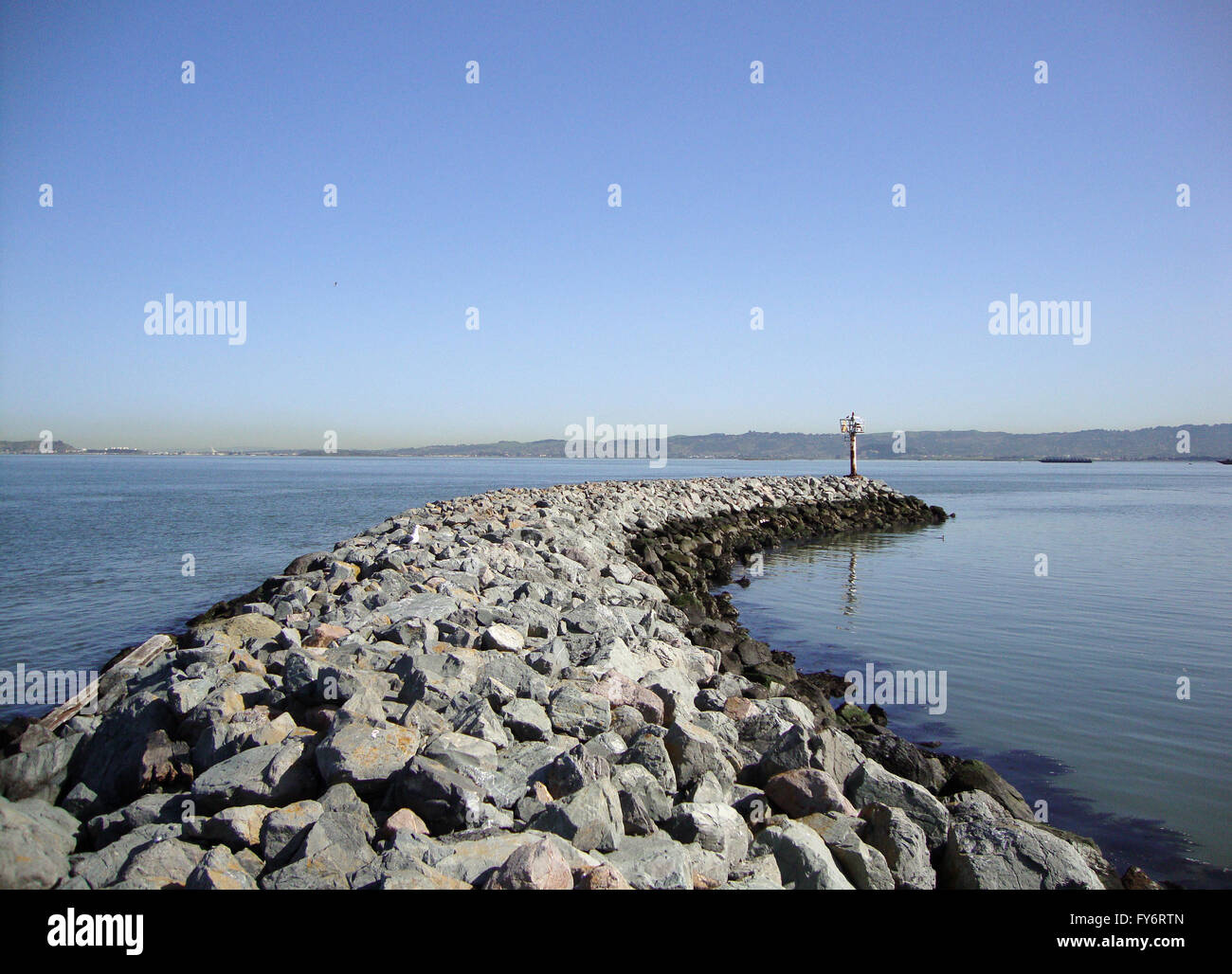 Curved Rock Jetty with light beacon at end in San Francisco Bay. - Stock Image