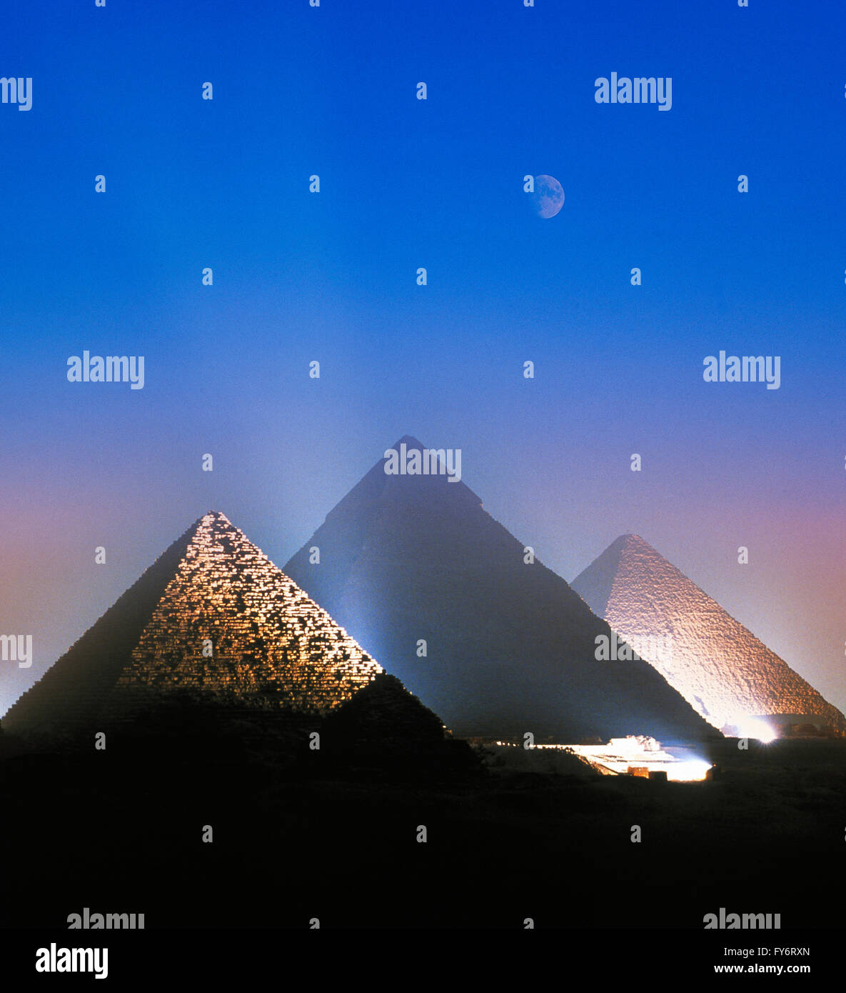 Moon over the illuminated Pyramids at Giza, Cairo, Egypt - Stock Image