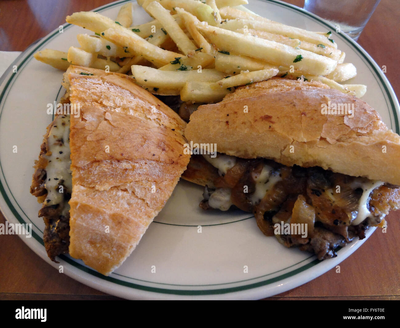 Philly Cheese Steak Style Sandwich And French Fries On A White Plate Stock Photo Alamy
