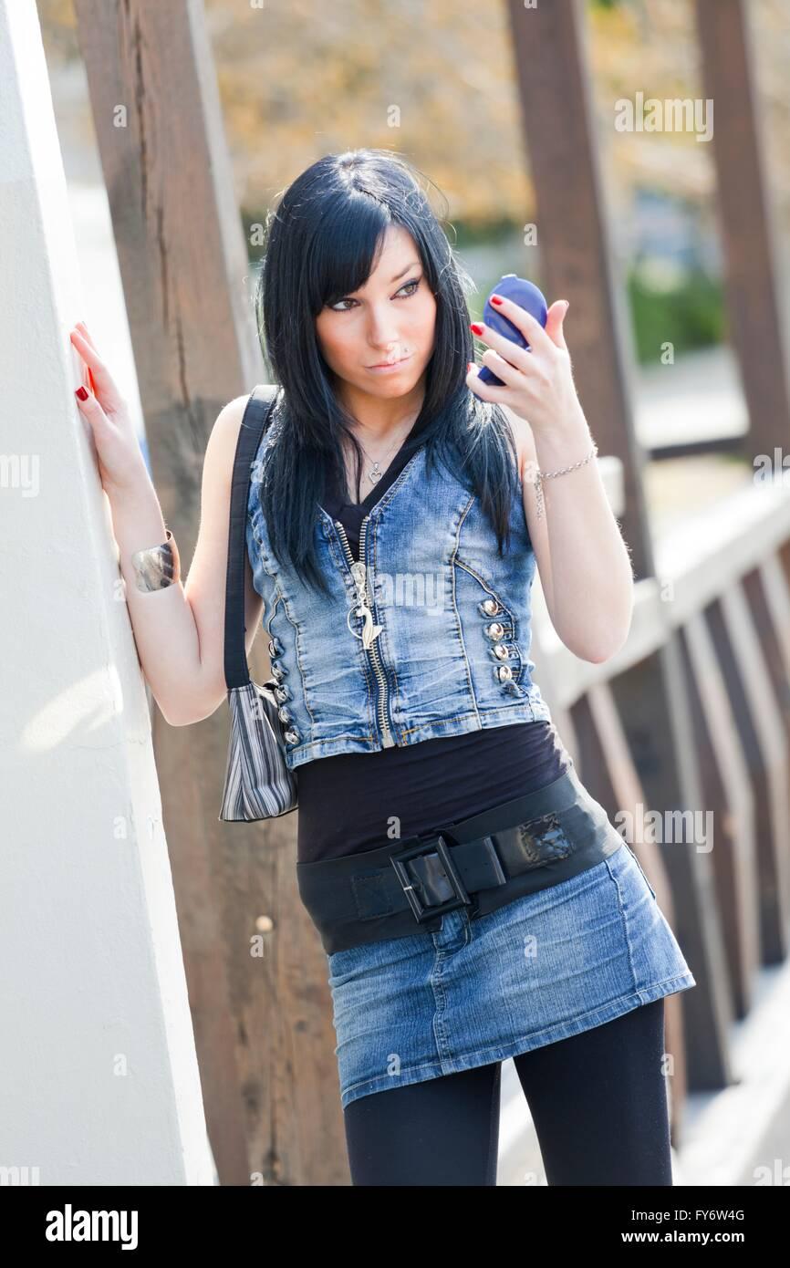 Teenager girl wearing denim clothes facing camera standing looking at handy mirror - Stock Image