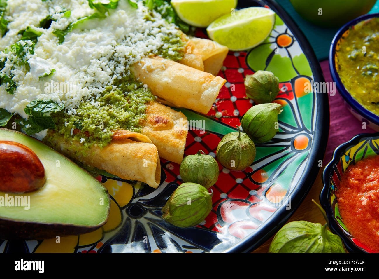 Green enchiladas Mexican food with guacamole and sauces on colorful table Stock Photo