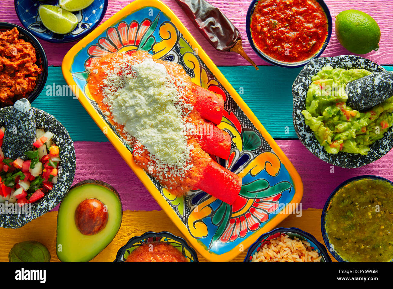 Red enchiladas Mexican food with guacamole and sauces on colorful table Stock Photo