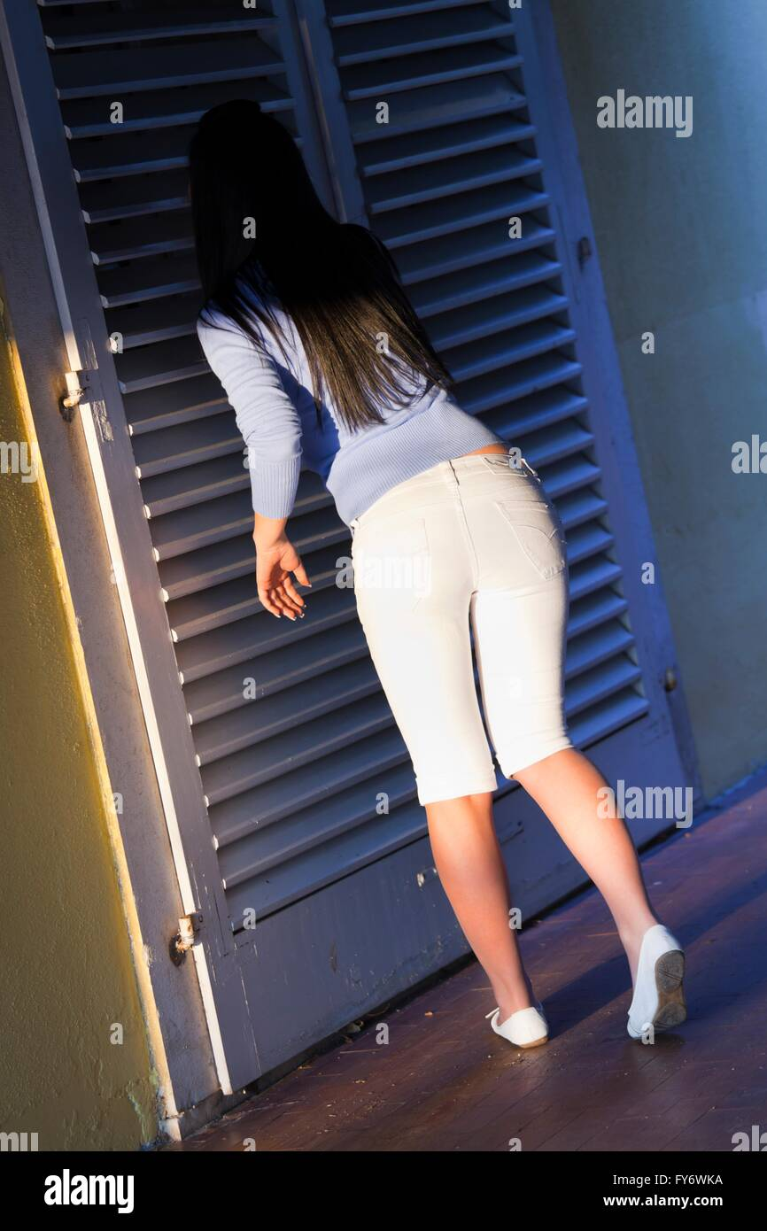 Teenager girl young woman White pants Summer from rear back rear-view rearview behind peeking inside venetian blinds Stock Photo