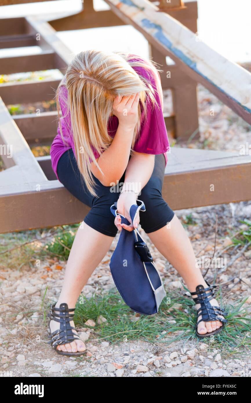 Tired young woman lifestyle girlnextdoor girl next-door outdoors desperate desperation bad mood hide hiding face - Stock Image