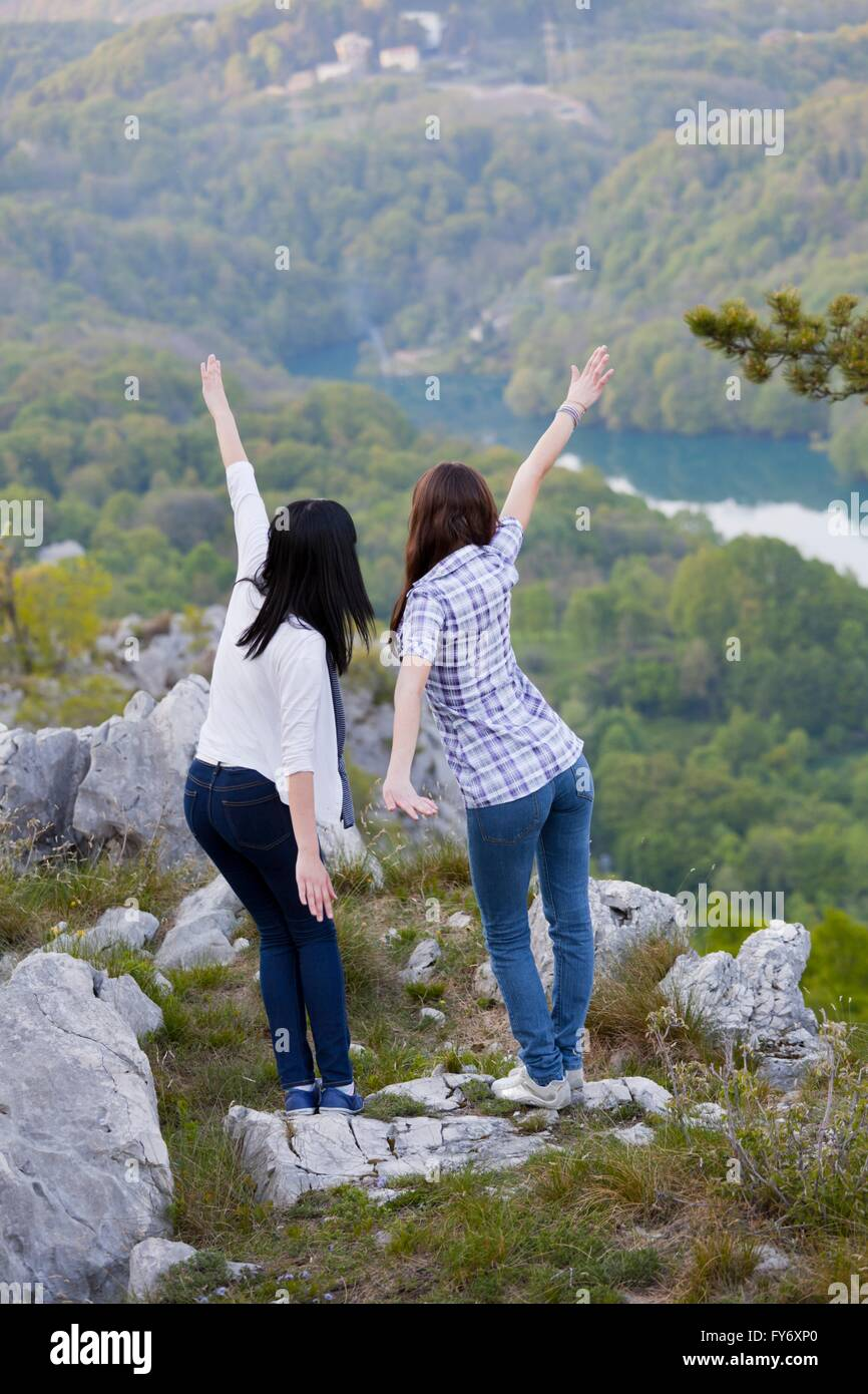 Pretend pretending to fly flying friendship friend friends spread hands arms nature rearview - Stock Image